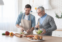 Senior Elderly Caucasian Old Father Teaching His Son How To Cook Dinner, Lunch, Prepare Food And Meal In The Kitchen Together. Happy Father`s Day! I Love You, Dad!
