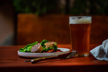Slices Of Grilled Sausage With Spinach And Red Pepper And A Pint Of Beer
