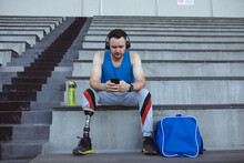 Caucasian Male Athlete With Prosthetic Leg Using Smartphone Sitting On The Seats In The Stadium