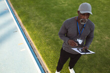 African American Male Coach With Clipboard And Digital Tablet Standing Near The Running Track