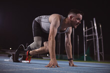 Caucasian Male Athlete With Prosthetic Leg In Starting Position For Running On The Track At Night