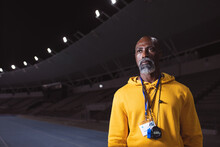 African American Senior Male Coach Standing On The Running Track At Night