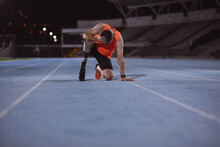 Disappointed Caucasian Male Athlete With Prosthetic Leg With Hand On Head Sitting On Running Track