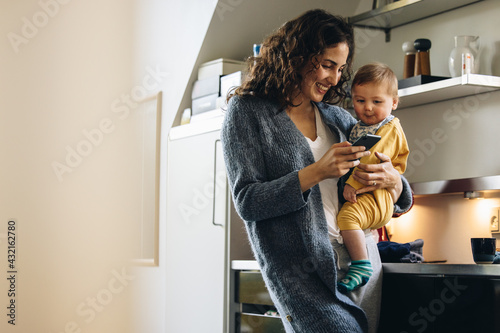 Fototapeta Smiling woman with baby texting on phone at home obraz
