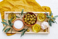 Overhead View Of Three Different Pots Of Olive Oil With Olives, Garlic  And Seasoning On A Tray