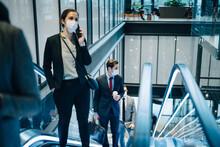 Businesswoman Talking Through Smart Phone While Moving Upwards On Escalator During Pandemic