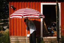 Man Unfolding Parasol In Front Of Shed