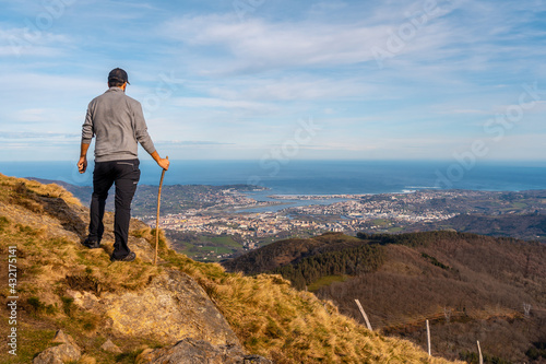 A young man in a gray sweater looking at the views of the towns of Hondarribia and Hendaya from the mountains of Aiako Harria or Peñas de Aya, Guipúzcoa. Basque Country