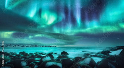 Northern lights. Aurora borealis over ocean in Teriberka, Russia. Starry sky with polar lights and clouds. Night winter landscape with bright aurora, stars, sea, snowy stones in blurred water. Travel