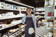 Portrait of smiling female owner with hand on hip in deli store