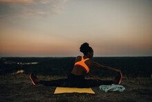 Rear View Of Female Athlete Doing Yoga During Sunset