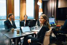 Portrait Of Female Lawyer Sitting With Colleagues During Meeting In Office
