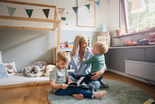 Cheerful Mother Playing With Children In Bedroom