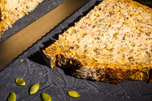 Slice Of Rustic Natural Yeast-free Bread With Flax, Poppy Seeds, Sesame Seeds, Millet, Pumpkin And Sunflower Seeds, With Olive Oil In A Glass Jar, And A Knife, On A Black Background, Hard Light