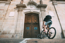 Boy With A Backpack On A Bike In Front Of A Wooden Door Of A Church . Background With Copy Space. Sport Concept. Urban Cycling Concept. Live Style Concept
