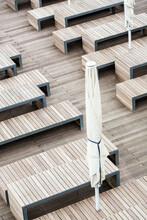 Bänke Und Sitzreihen Aus Holz Auf Einer Holzterrasse Mit Zugeklappten Sonnenschirm.