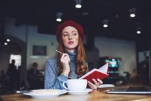 Thoughtful Elegant Female Writing In Notebook In Modern Cafe