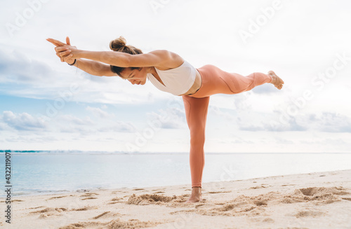 Slender young woman performing Virabhadrasana C yoga position on sandy beach - fototapety na wymiar