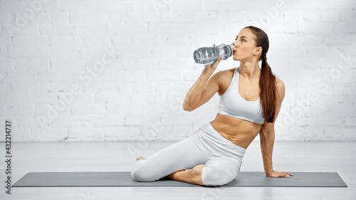 Obraz Sportswoman in white sportswear training at home. - fototapety do salonu