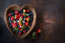Assorted Fresh Berries In A Heart-shaped Wooden Bowl