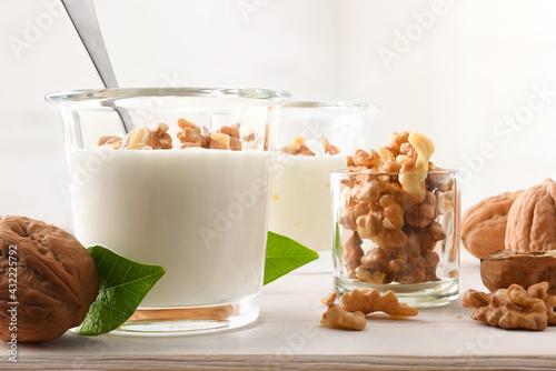 Fototapeta Yogurt with walnuts pieces in glass on wood bench obraz