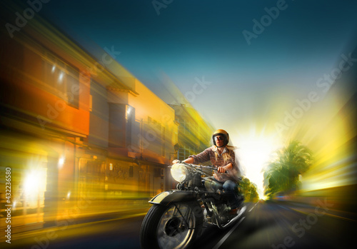 Female biker on the sunset boulevard with old motorbike. Fototapeta