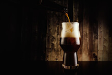 Pouring Dark Beer Into The Glass From The Bottle On Wooden Background.