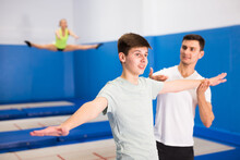 Skilled Coach Holding Training With Teenager In Trampoline Room, Explaining Basic Jumping Tricks..
