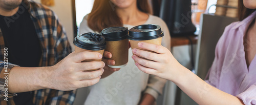 Obraz Closeup of a group of young people enjoyed drinking and clinking coffee cups together in cafe - fototapety do salonu