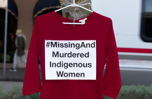 """A Red Dress With Text """"Missing And Murdered Indigenous Women"""" Is Hanging On The Tree. Art Memorial To Honour Missing And Murdered Indigenous Women In US And Canada"""