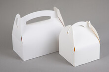 Two White Blank Paper Packaging For Bakery Large And Small Box With Handle In Grey Background