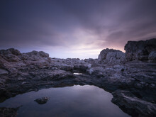 Eerie Scenery Of Rocky Outcrops In The Ocean Under The Purple Sky