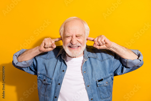 Fototapeta Photo of unhappy irritated upset old man close ears fingers bad mood loud noise isolated on yellow color background obraz