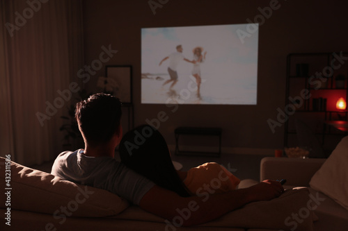 Fototapeta Couple watching movie on sofa at night, back view obraz