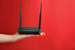 Leinwandbild Motiv Woman holding modern Wi-Fi router on red background, closeup. Space for text