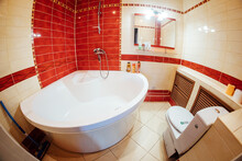 A Bathroom With A Huge Bathtub. Cozy Bathroom With Toilet. Clean Red Tiles On The Walls. Mirror And Hot Water Mixer