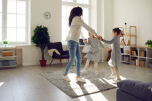 Joyful Active Happy Family Having Fun Enjoy Leisure At Home. Young Mother Dancing With Daughters Children Together In Living Room. Carefree Mum With Cheerful Kids And Funny Weekend Activities