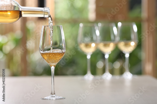 Pouring white wine from bottle into glass on table against blurred background, space for text - fototapety na wymiar