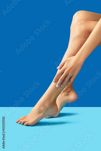 Obraz Female legs and hands with fashionable blue nail design - fototapety do salonu