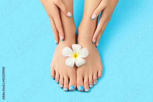 Manicure, pedicure beauty salon concept. Womans feet on blue background