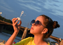 Beautiful Young Girl With Round Sunglasses And Yellow Clothes Blowing Soap Bubbles  Summer Rays Of The Setting Sun Outdoors On The Embankment Against The Blue Sky