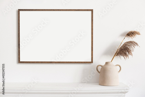Fototapeta Blank picture frame mockup in home interior design. Living room, commode with lamp and vases. View of modern scandinavian style interior with artwork template on a white wall. obraz