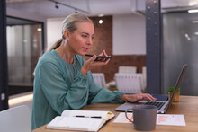 Caucasian Woman Talking On Smartphone While Using Laptop At Modern Office