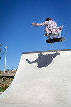 Back View Of Caucasian Man Jumping And Skateboarding On Sunny Day
