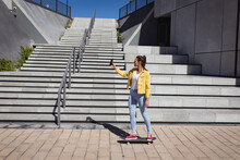 Smiling Caucasian Woman Standing On Skateboard And Taking Selfie Next To Stairs