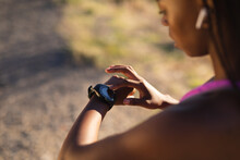 Fit African American Woman Checking Smartwatch During Exercise In Countryside