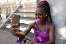 Smiling Fit African American Woman Taking Selfie With Smartphone During Exercise In City