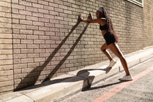 Fit African American Woman Stretching Leaning Against Brick Wall Exercising In City