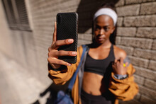 Fit African American Woman With Gym Bag Taking Selfie With Smartphone Standing By Brick Wall In City