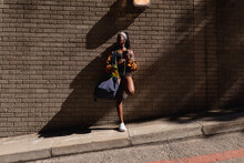 Fit African American Woman With Gym Bag And Water Bottle Leaning Against Brick Wall In City